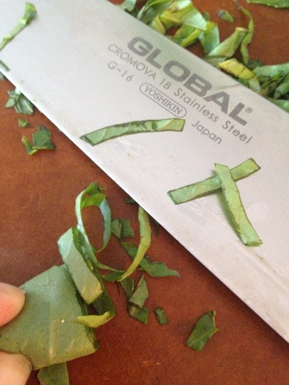 To make chiffonade, roll up a stack of basil leaves and slice thinly.