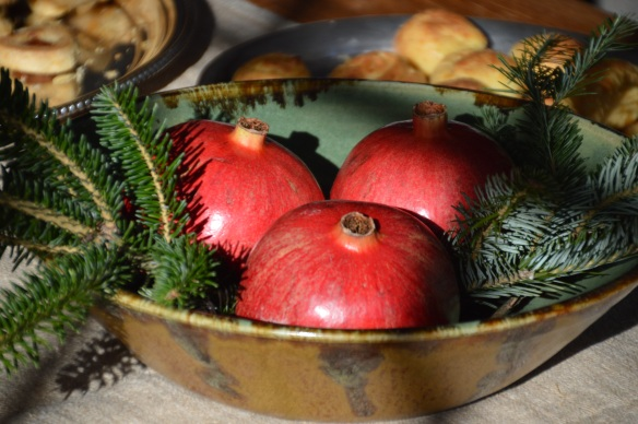 A last-minute centerpiece: pomegranates and Christmas tree trimmings in a bowl.