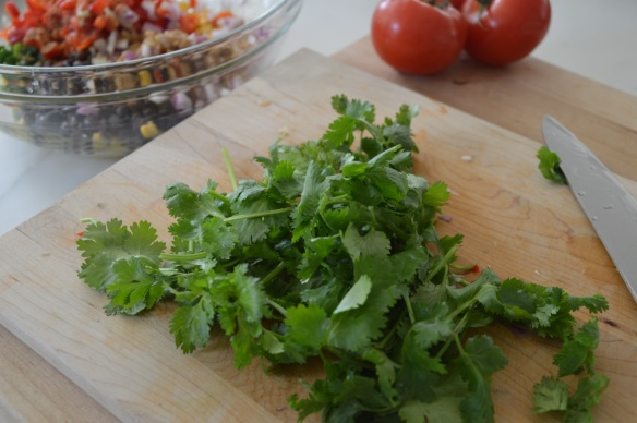 Twist off the root ends of a cilantro bunch. (Stems are OK, though.) Wash and spin as if it were lettuce. Chop the leaves and stems.